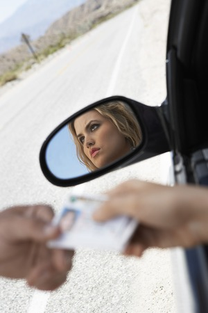 drivers license: Woman Handing a Police Officer her License