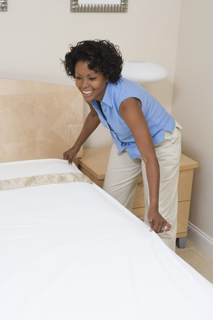 ベッドを作る女性 写真素材