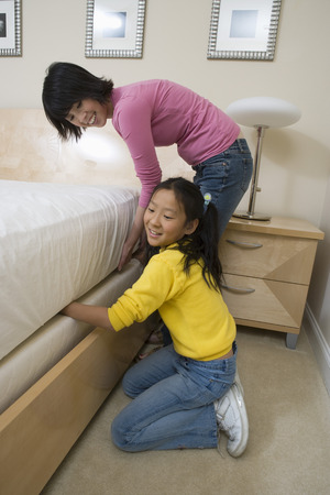 Mid-adult woman and her daughter making a bed Stock Photo - 5460093