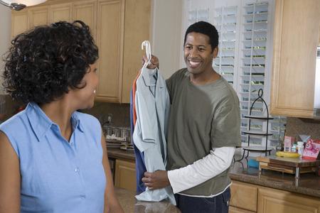 台所で服を抱きかかえたで半ば大人カップル 写真素材