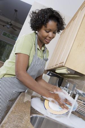 半ばの大人女性の洗浄の皿、笑みを浮かべて