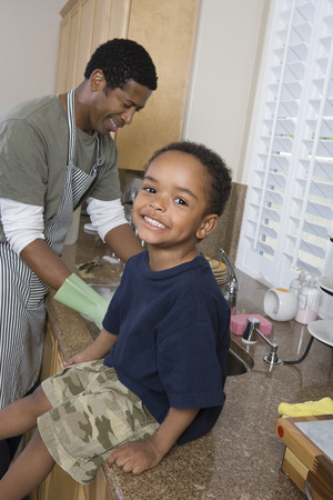 kitchen counter: Father washing dishes, son sitting on kitchen counter and smiling LANG_EVOIMAGES