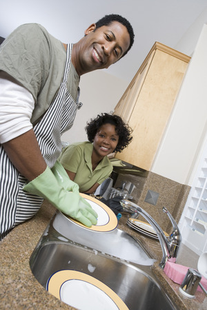 半ば大人男皿洗い、キッチン カウンターに傾いている彼のガール フレンドの笑顔 写真素材 - 5460121