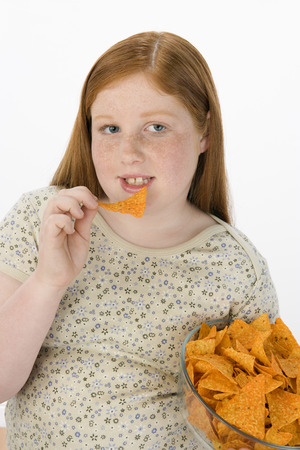 Overweight girl eating potato chips Stock Photo - 5460230