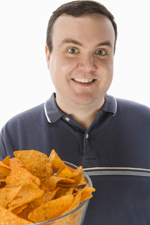 Mid-adult man holding glass bowl of potato chips Stock Photo - 5460235