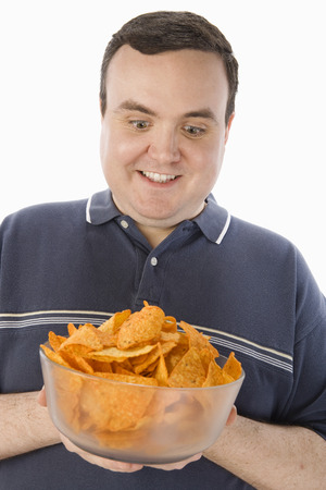 Mid-adult man holding glass bowl of potato chips Stock Photo - 5460238