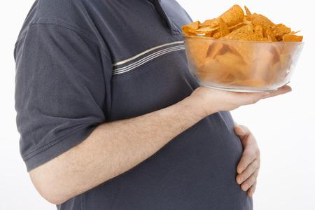 comida chatarra: Mediados de los adultos hombre con bol de cristal de patatas fritas, la secci�n media de