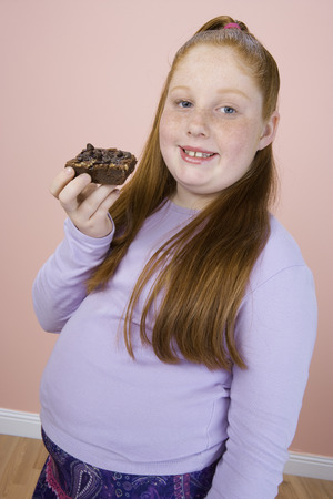 Overweight girl holding brownie, portrait Stock Photo - 5460269