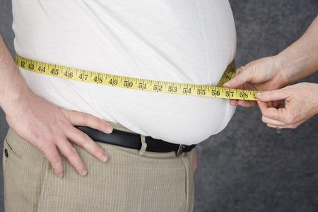 pancia grassa: Donna cintola di sovrappeso uomo con la misura di nastro, sezione centrale di misura