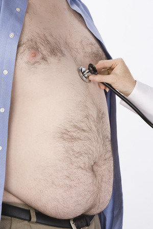 Doctor hand with stethoscope on overweight man's heart,, mid section Stock Photo - 5460279