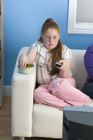 Overweight girl watching television on sofa Stock Photo - 5460285