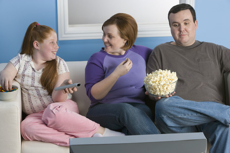 obese girl: Overweight family watching television on sofa