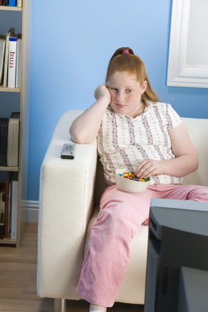 childhood obesity: Overweight girl watching television on sofa