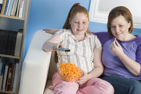 obese child: Overweight girl and mother watching television on sofa