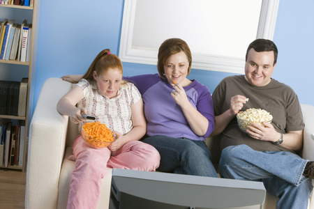 obese child: Overweight family watching television on sofa