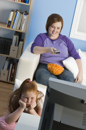 Overweight girl and mother watching television Stock Photo - 5460292