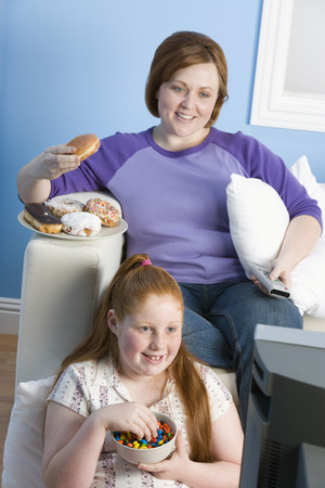 obese child: Overweight girl and mother watching television, eating