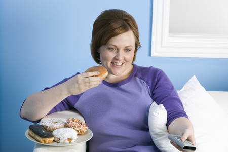 unhealthy living: Overweight woman watching television, eating LANG_EVOIMAGES