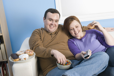 Overweight couple watching television on sofa Stock Photo - 5460298