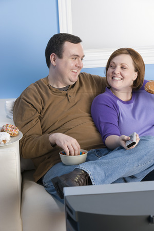 unhealthy living: Overweight couple eating on sofa LANG_EVOIMAGES