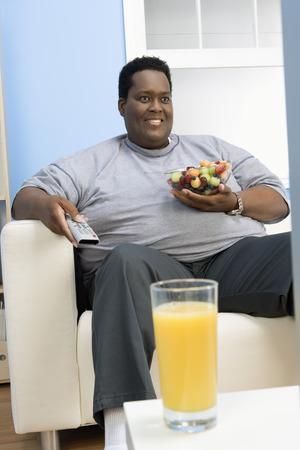 太りすぎの人はテレビを見て、健康を食べる 写真素材