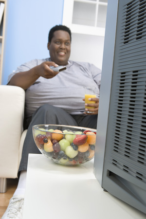 healthily: Overweight man watching television, eating healthily