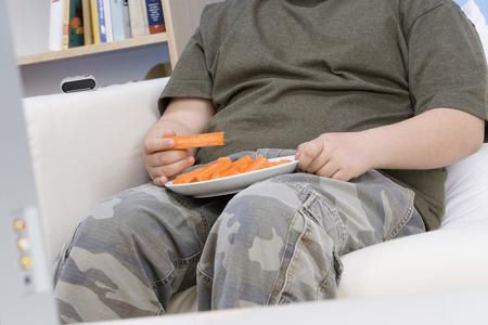 obesidad infantil: Ni�o con sobrepeso que comer zanahorias en sof�, mid-section