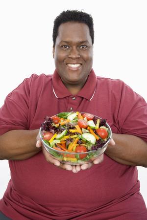 サラダを保持している太りすぎの男のスタジオ ポートレート