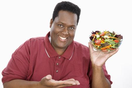サラダを提示する太りすぎの男のスタジオ ポートレート
