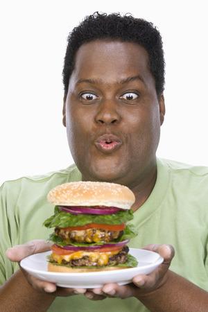ミッド アダルト太りすぎ人大きなチーズバーガーとプレートを保持しています。