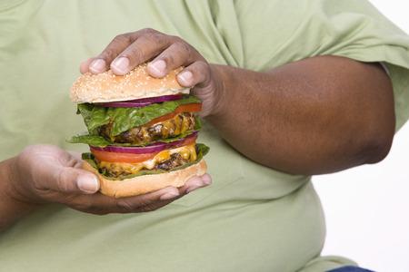 半ば大人肥満男は大きなチーズバーガーを保持しています。 写真素材 - 5460340