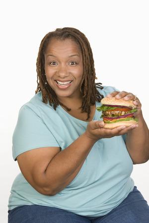 大きなチーズバーガーを保持していると笑みを浮かべての半ば大人肥満女性の肖像画 写真素材 - 5460342