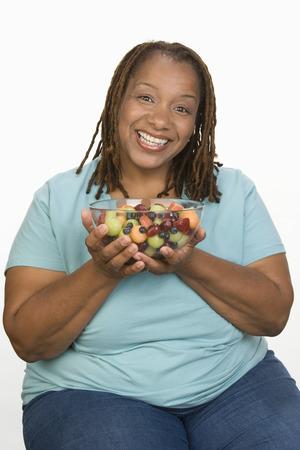 半ばの大人の肥満女性保持ボウルの肖像ウィット フルーツ サラダと笑みを浮かべて 写真素材 - 5460343