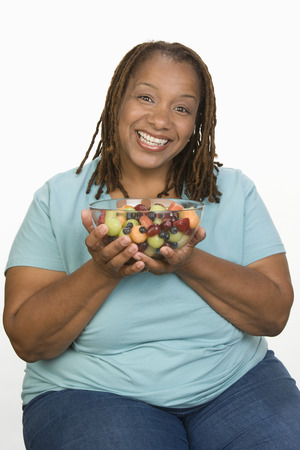 Portrait of Mid-adult overweight  woman holding bowl wit fruit salad and smiling Stock Photo - 5460343