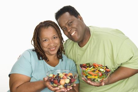 半ばの大人の肥満女性と半ば大人太りすぎ人間果物と野菜のサラダ ボウルを保持笑みを浮かべて 写真素材 - 5460347