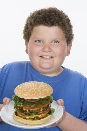 太りすぎの大きなチーズバーガーとプレートを持つ男の子
