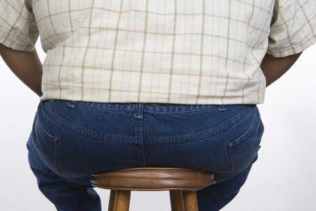 man in jeans: Overweight mid-adult man sitting on chair, back view