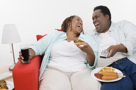 ミッド アダルト太りすぎカップル食事と一緒にソファに座ってテレビを見る