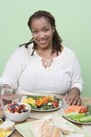 健康的な食事を持っている太りすぎの半ば大人女性 写真素材