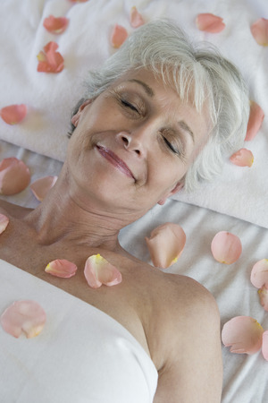 the ageing process: Senior woman covered in petals on bed