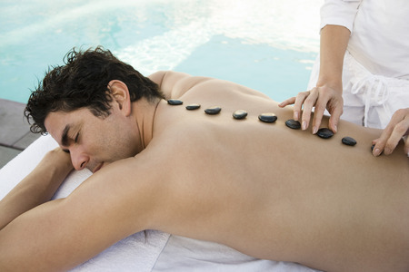 the ageing process: Man having stone therapy by swimming pool