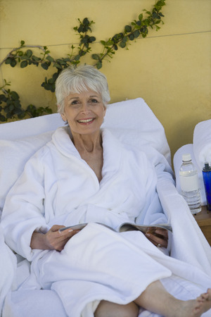 the ageing process: Portrait of senior woman in bathrobe at health spa LANG_EVOIMAGES