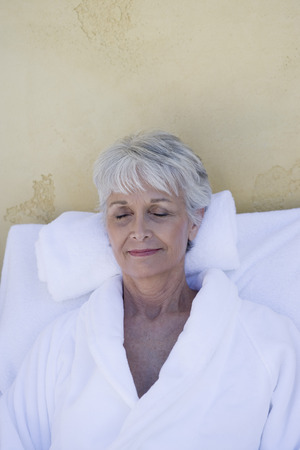 the ageing process: Senior woman in bathrobe at health spa LANG_EVOIMAGES