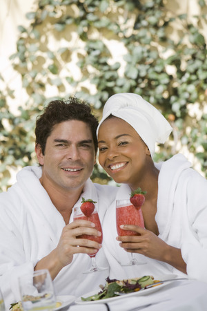 Portrait of couple in bathrobes, drinking at health spa Stock Photo - 5470092
