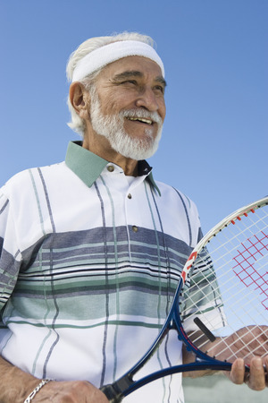 tennis racket: Senior man holding tennis racket