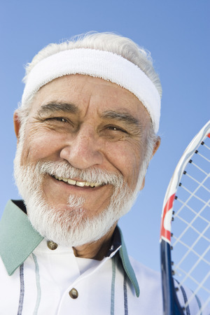 tennis racket: Senior man holding tennis racket, portrait LANG_EVOIMAGES