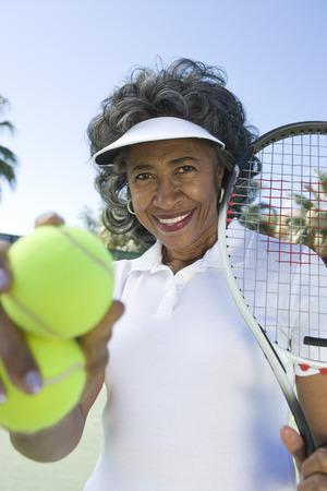 テニスのラケットとボール、肖像画を保持している年配の女性