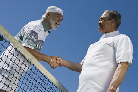 テニスのネット上の手を振る 2 人の男性