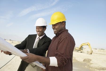 Landvermesser und Bauarbeiter auf Website