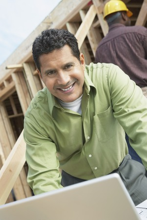 early 30s: Construction Worker Using Laptop on Site